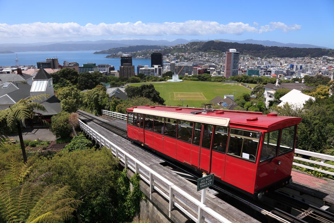 A tram descends down a hillside to a city built on the waterside