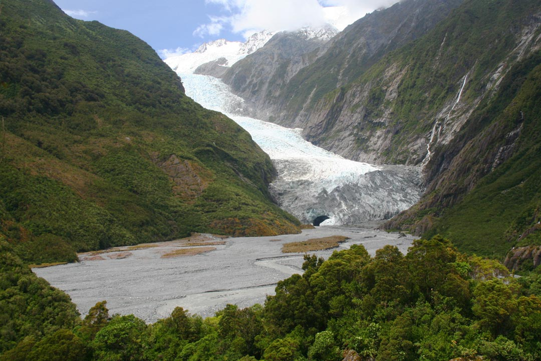The icey Franz Josef glacier cuts down through green and rocky mountain faces