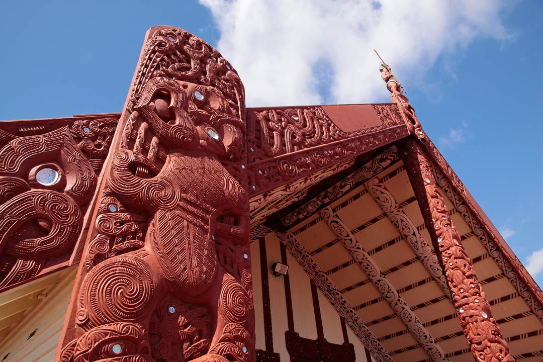 A close-up of ornate Maori carvings attached to a building