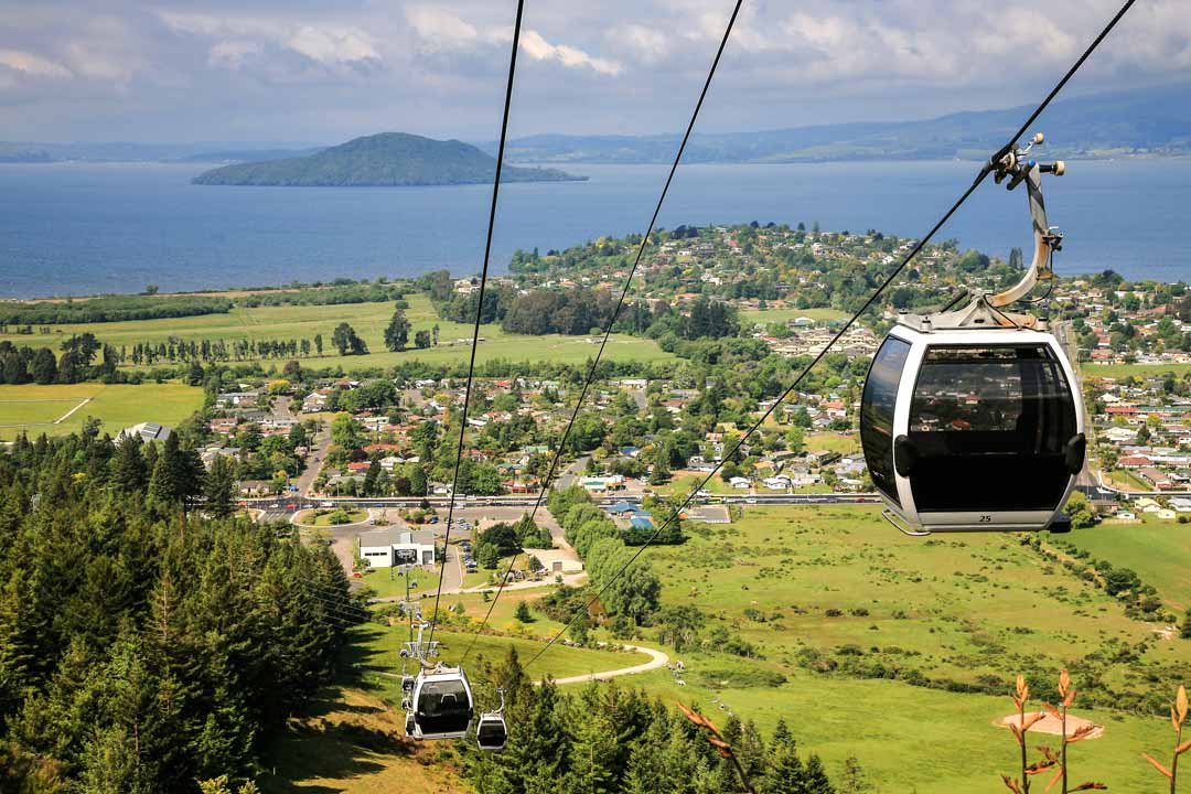 Cable cars ascend with green fields and trees below, in the distance is a rocky island surrounded by a body of water.