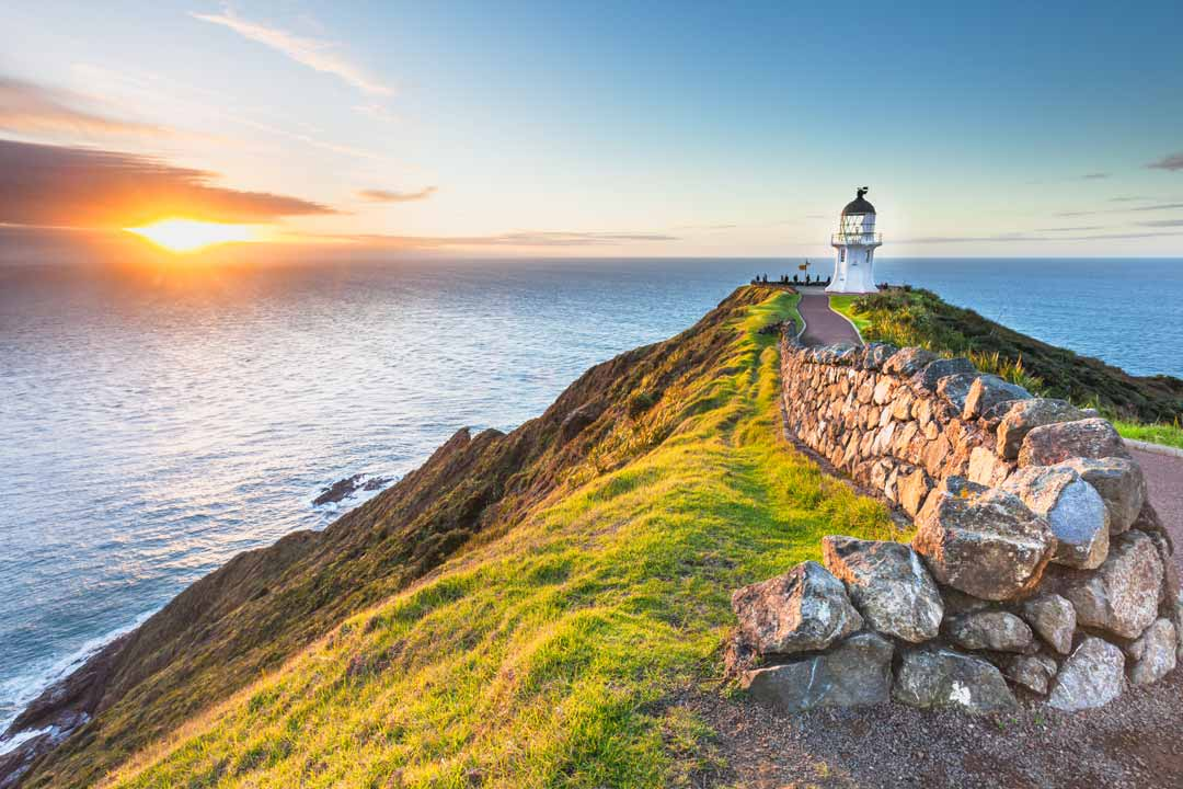A stone wall and path leads out along a narrow head of land to a lighthouse and then the sea