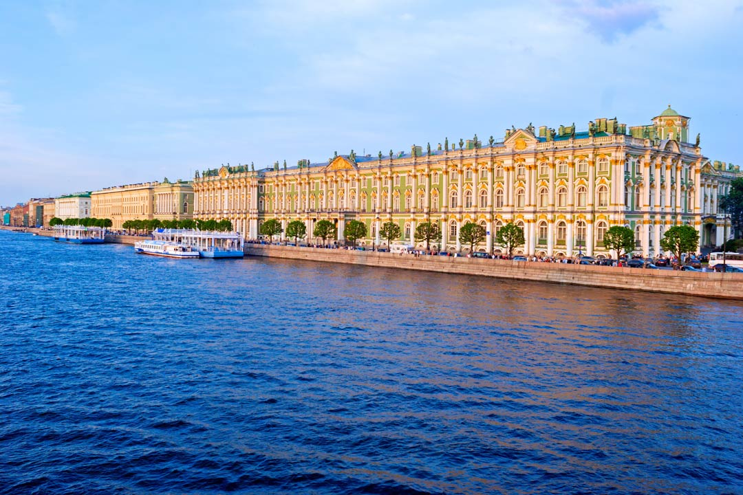 A palace decorated with gold stands in front of a wide blue river, the boulevard in front is lined with green trees and leads to river cruise boats.