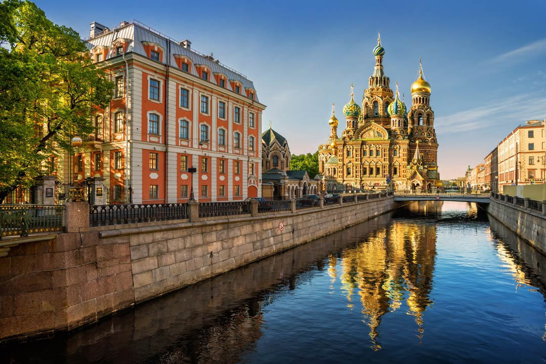 A river runs tranquilly to an ornate golden palace with domes and spires built in the Eastern style