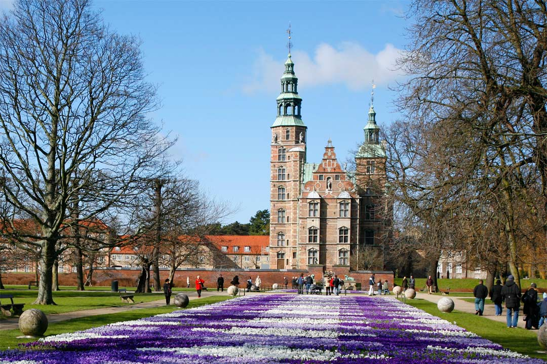 A flowerbed made up of blue, purple and white flowers leads to a palace with two towers with narrow spires on top.