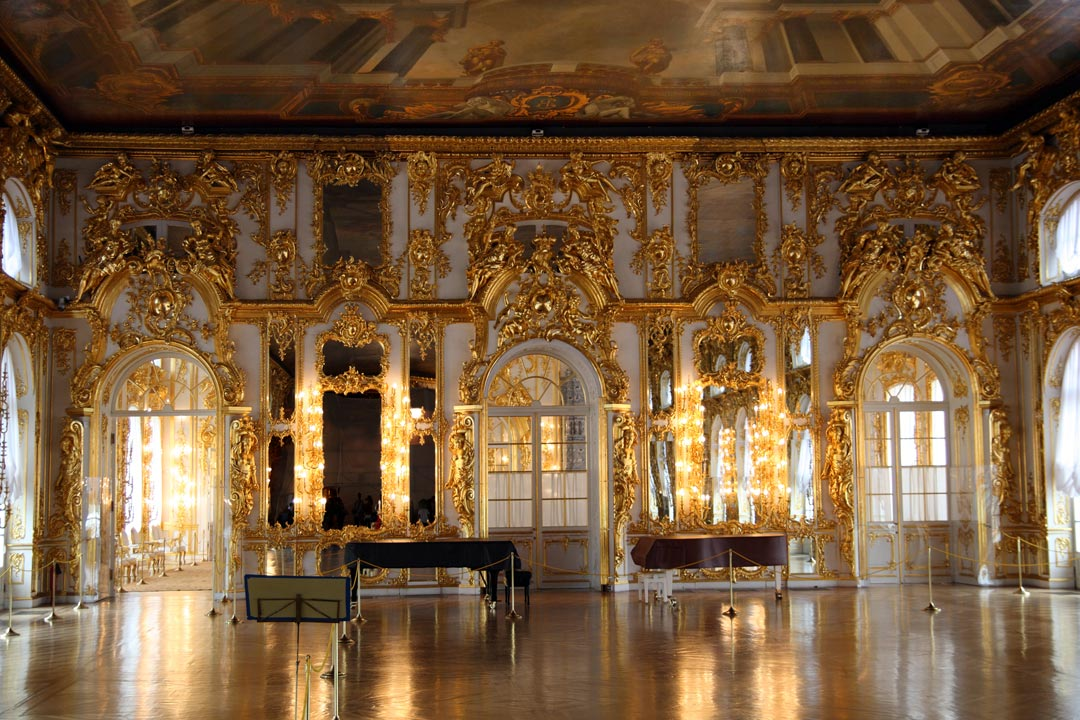 The interior of a luxurious palace. The far wall has high doorways and the wall is covered in huge amounts of gold forming figures and decorative patterns.