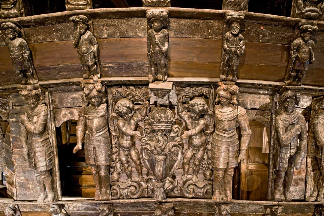 Ornate metal figures attached to wooden paneling, including soldiers in suits of armour and cherubs.