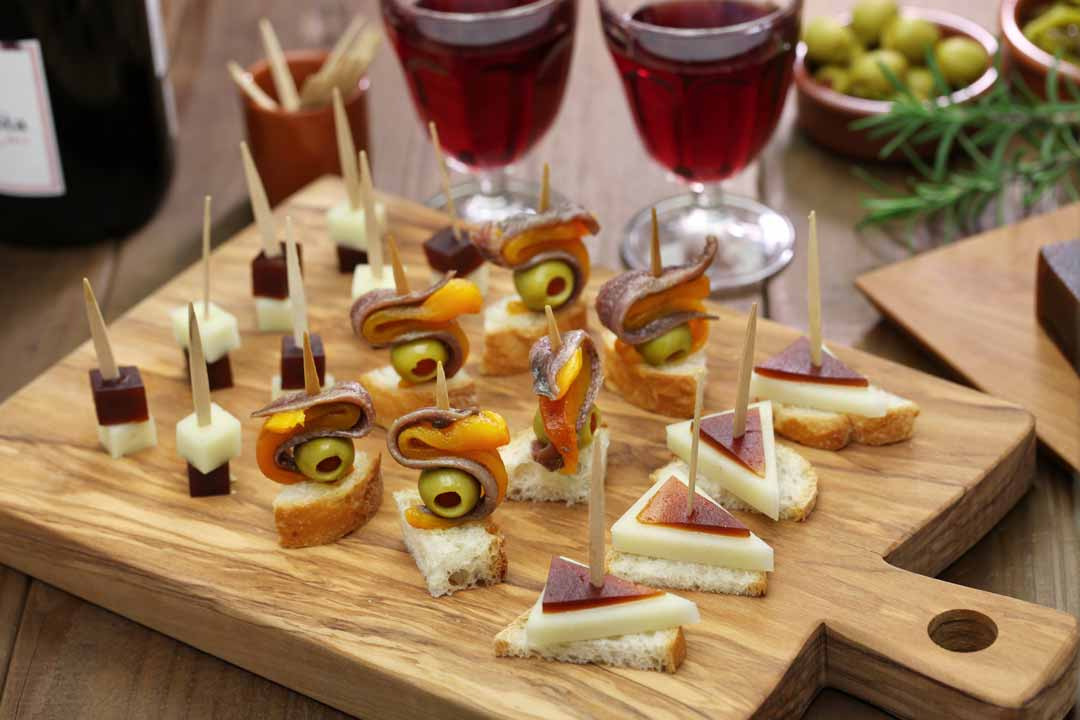 A selection of pintxos, including, cheese, olives and cured meats. Two glasses of dark red wine stand behind the platter