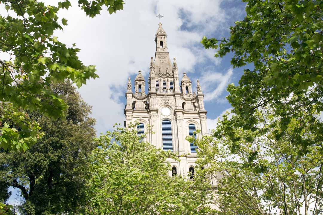 A cathedral surrounded by trees with a narrow tower with a crucifix on top