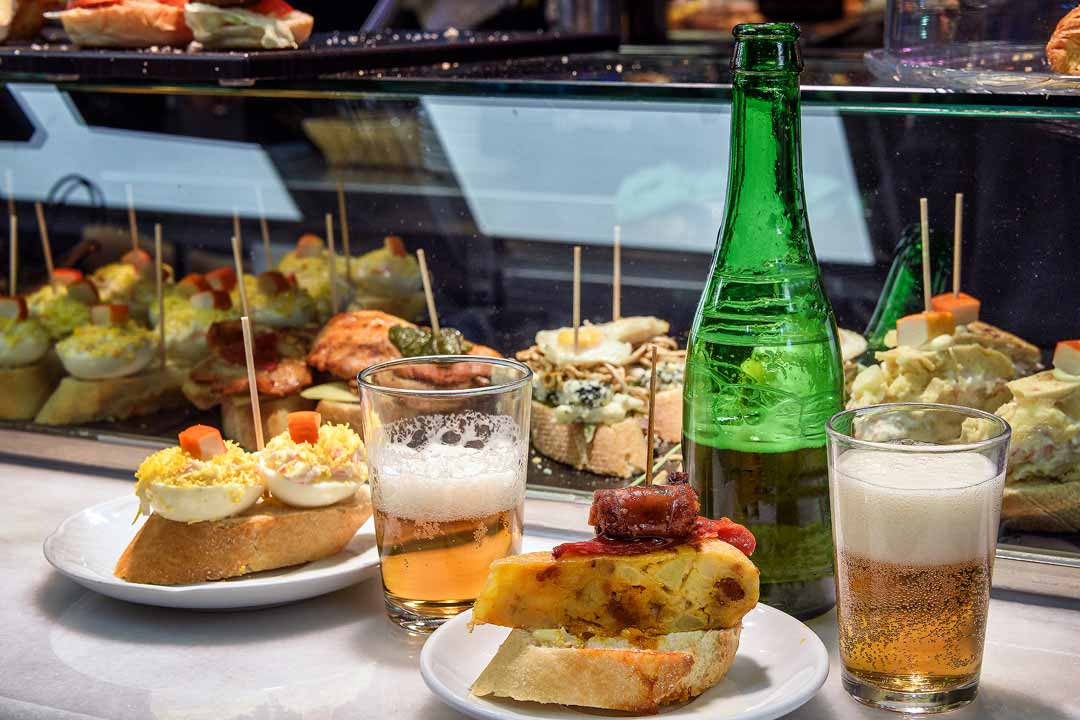 A variety of pintxos, various ingredients perched up top of bread. Two glasses of beer are on the table