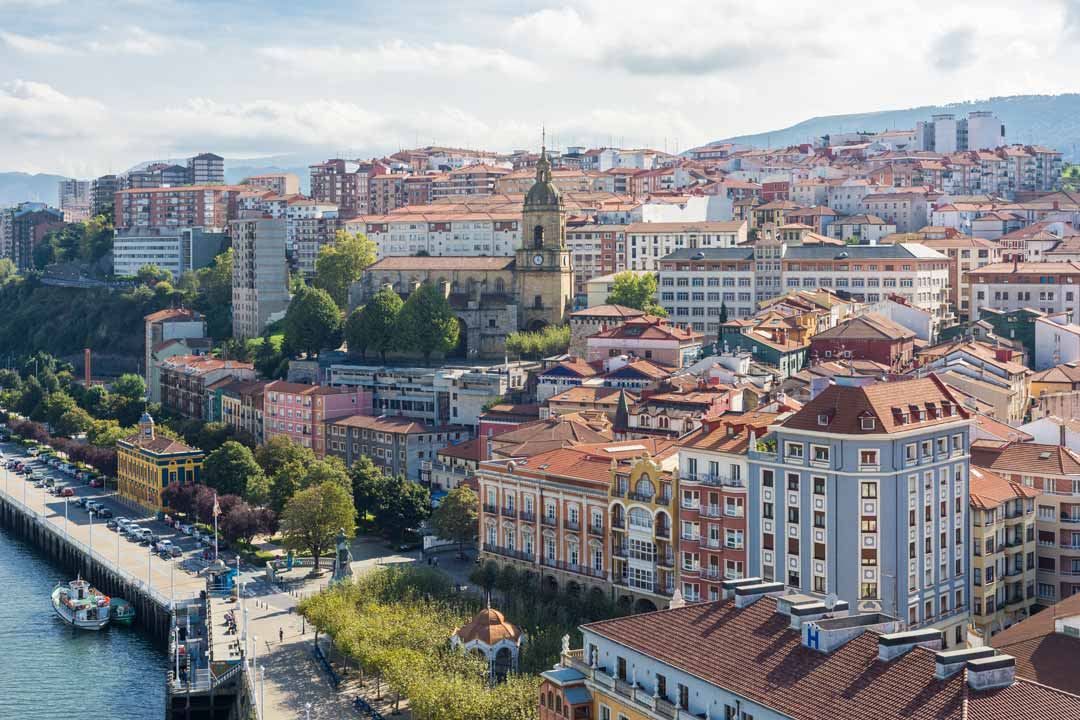 Bilbao riverside with buildings stretching up a hill, including an ornate church with spire