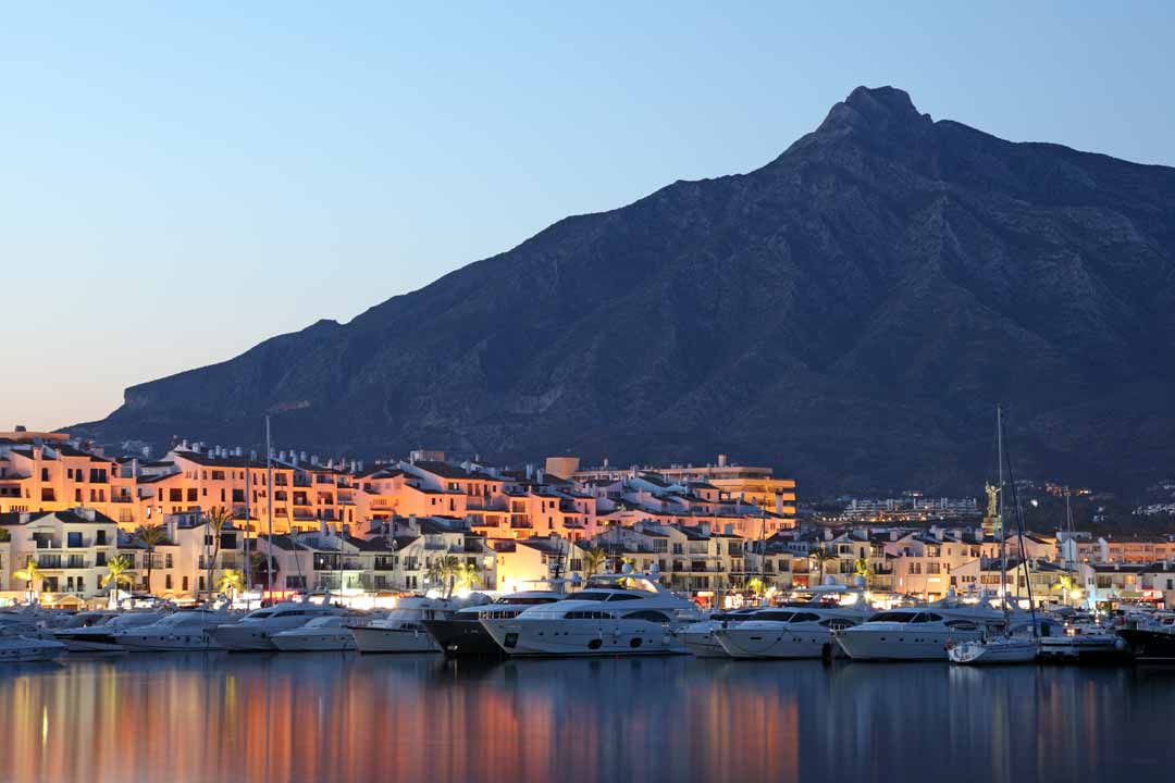 Yachts and motorboat are moored on a marina with white apartments overlooking the harbour. A mountain towers over in the background