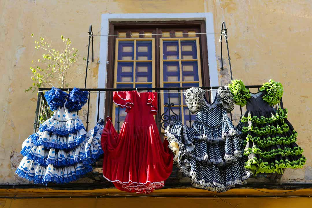 Traditional Spanish dresses, with thrills and bright colours hang from the balcony of a pastel house