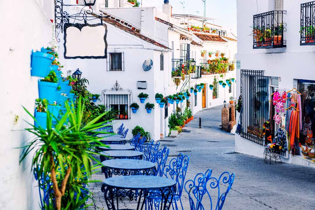 Typical white Spanish houses on a narrow street lined with hanging baskets and with blue tables and chairs