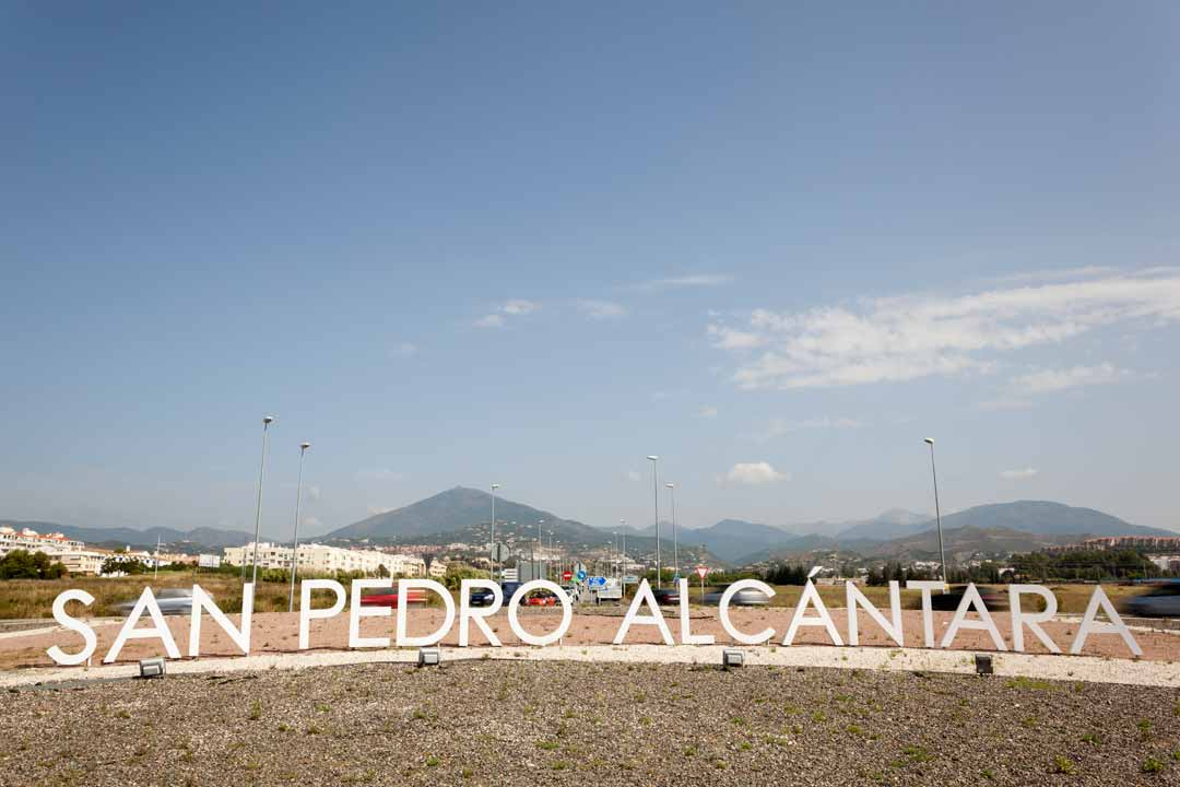A sign reads San Pedro Alcantara in big white letters with the mountains of Sierra de Ronda behind