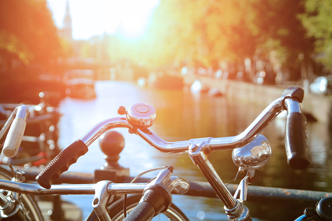 Bicycles on a bridge overlooking a canal under sun light