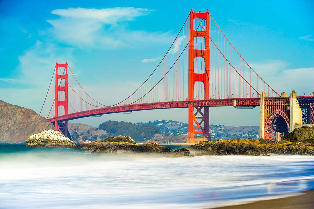 Golden Gate bridge towers over the bay filled with pure blue water