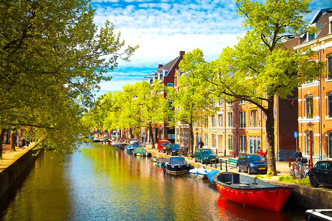 A canal is lined with small pleasure boats, tall town houses and bright green trees