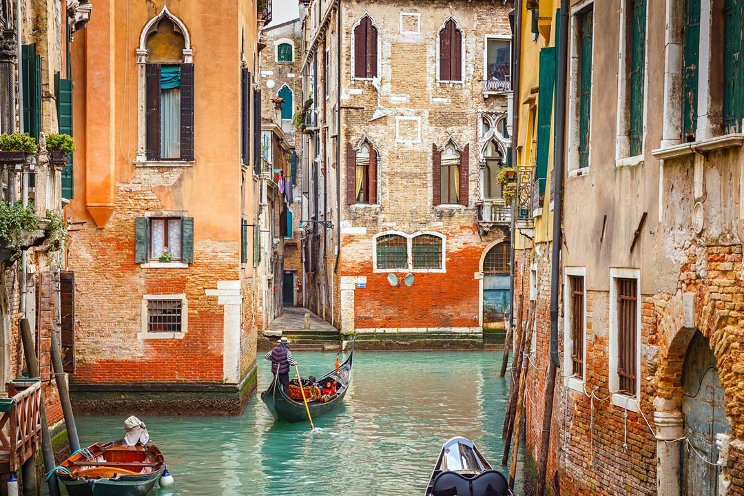 back canals of Venice showing crumbling houses and gondolas