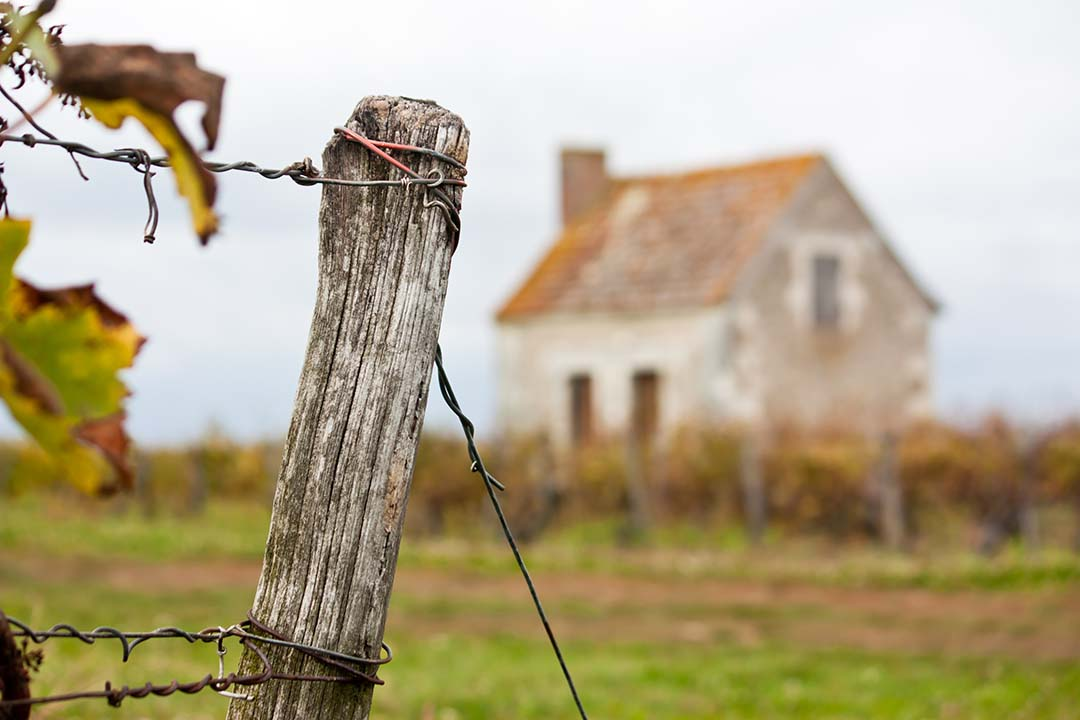 Wooden post in front of farmhouse