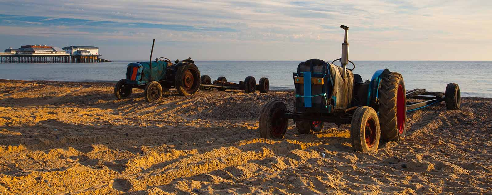 Two tractors on the beach sand in front of the water