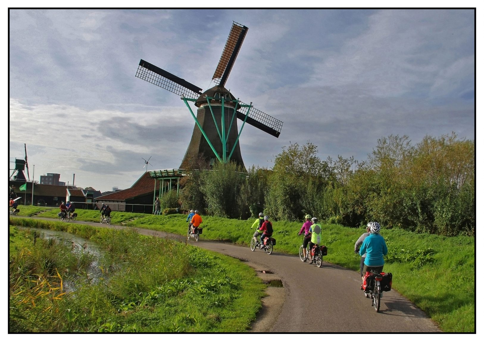 Tandem cyclysts infront of a windmill